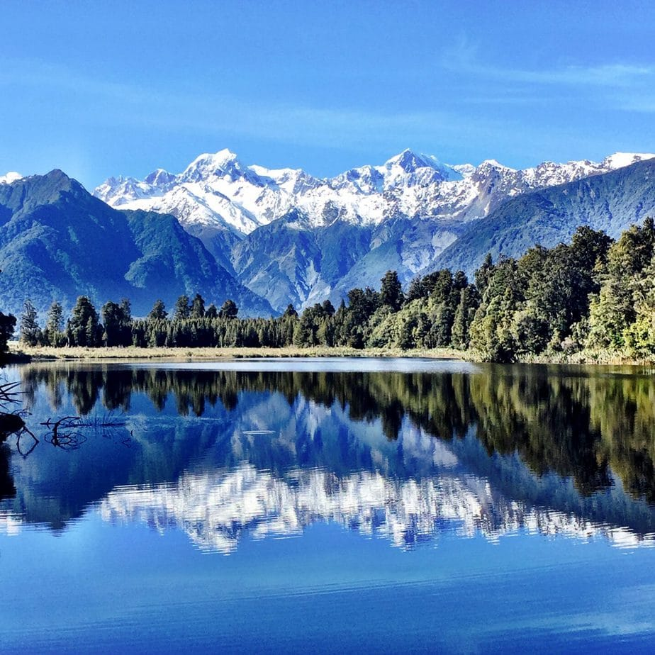 The snow capped mountain range perfectly reflected in Lake Matheson in New Zealand