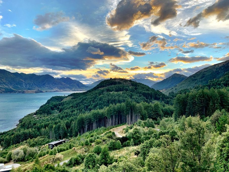 Sunset over the mountains, blue bay and green trees in Queenstown, New Zealand