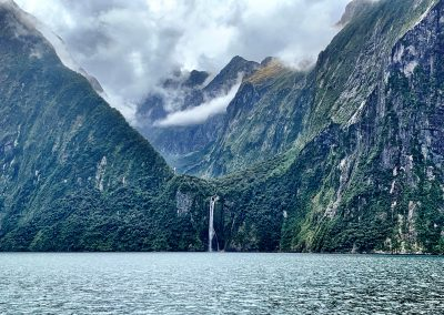 Waterfall at the bottom of a mountain crescent in Milford Sound, New Zealand