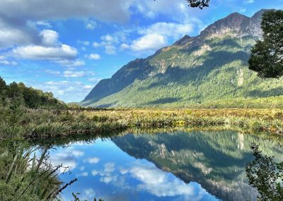 The mountains reflecting in the lake below at Reflection Lake in Fiordland National Park, NZ