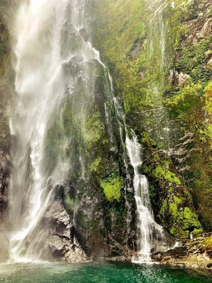 One big and one smaller waterfall surrounded by moss covered mountains in Milford Sound, NZ