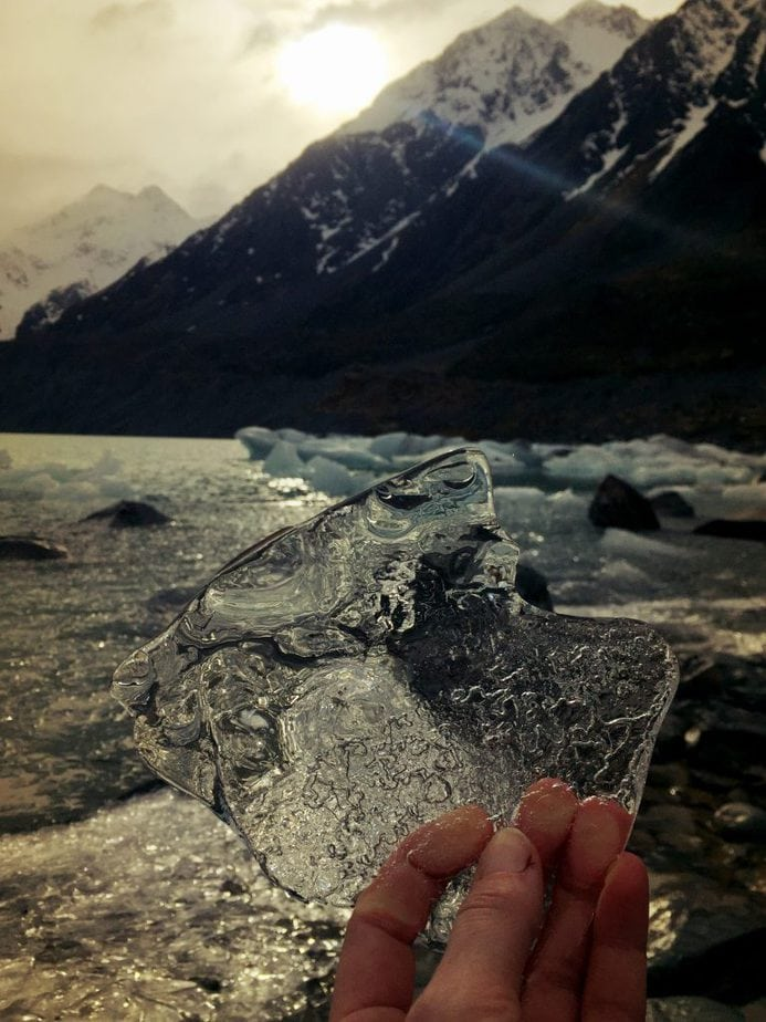 A hand holding up in their fingers a see through piece of glacier ice with the sun beginning to hide behind the mountains in the background.