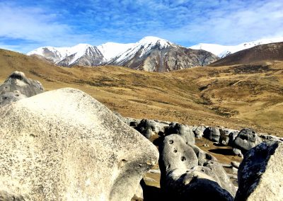 Boulders from Castle Hill will snow covered mountain range in the background