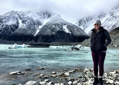 Me standing in front a lake with floating glaciers and snowy mountains in the background