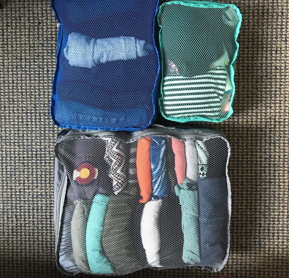 Clothes folded to the KonMari method and organized within packing cubes ready to go into a suitcase