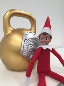 a cheeky elf on the shelf hanging out with the F45 Kettlebell