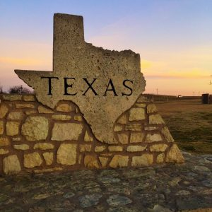 A stone landmark at the Oklahoma and Texas border at sunset in the shape of Texas and the words Texas written on it