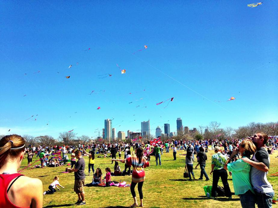 Kites flying in the sky with the Austin skyline in the background for the annual Austin Kite Festival at Zilker Park one of my favorite festivals in the city