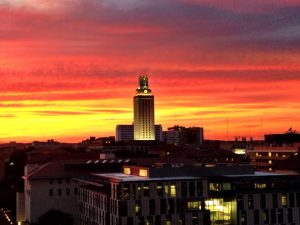 a red and orange sunset behind the University of Texas Tower in Austin, Texas