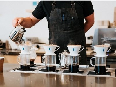 Barista pouring multiple cups of coffee at NYC Blue Bottle Coffee