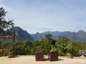 The backs of two empty chairs looking out over the vegetation and mountains of Laos.