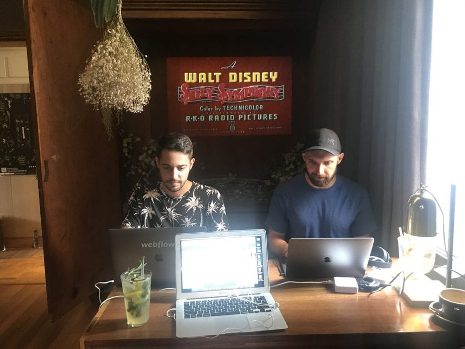 Remote Workers sitting at a table working from their laptops and at VERS House with old mickey mouse cartoons playing in the background