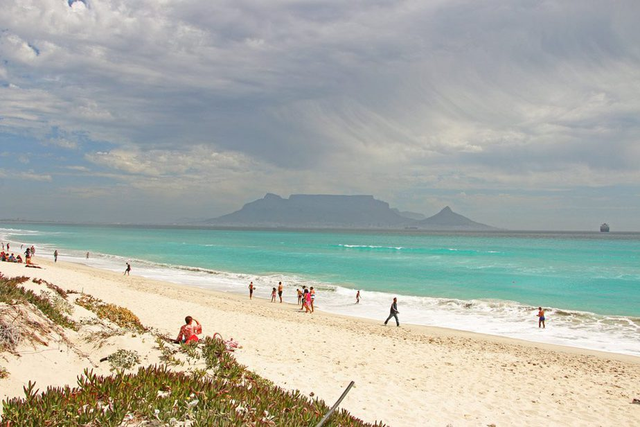 A beach in Cape Town with blue-green water and with people sitting and walking on its white sand shore