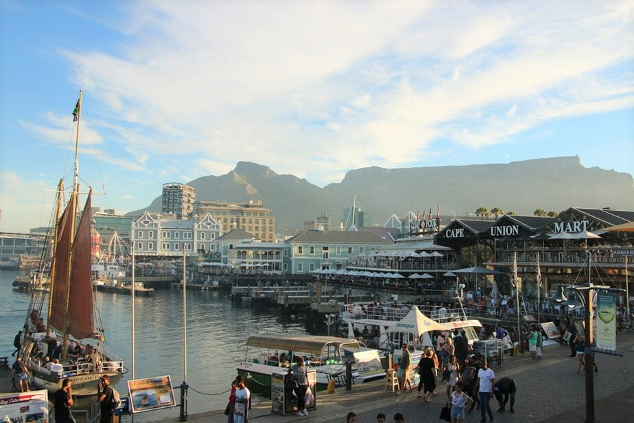 A busy bay in Capetown with yacht and boats on the water and people walking, sitting and talking, as well as cafes, buildings and marts