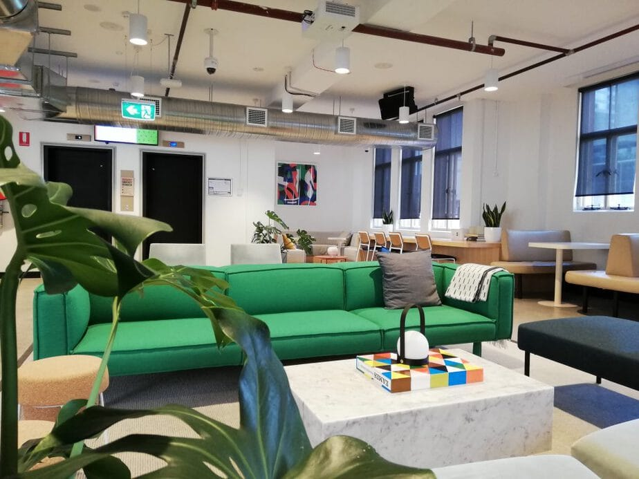 An office in Melbourne with long green couch and other office furniture
