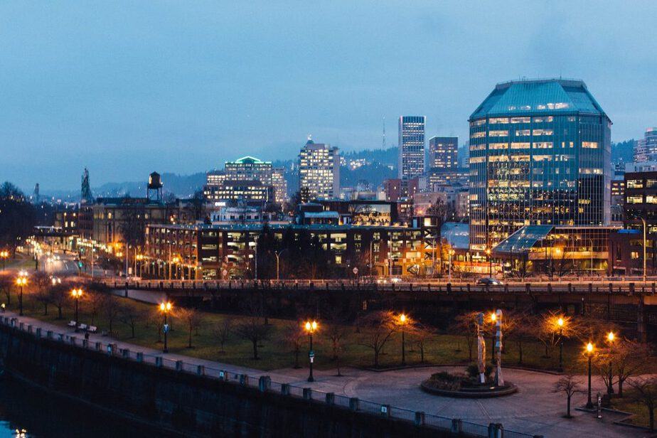 A picture of Portland Oregon at night with building and street lights shining bright