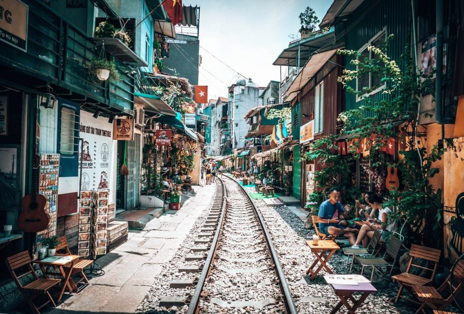 A railway in Hanoi Vietnam in between houses, stores and cafes and people sitting outside houses or cafes sitting and talking