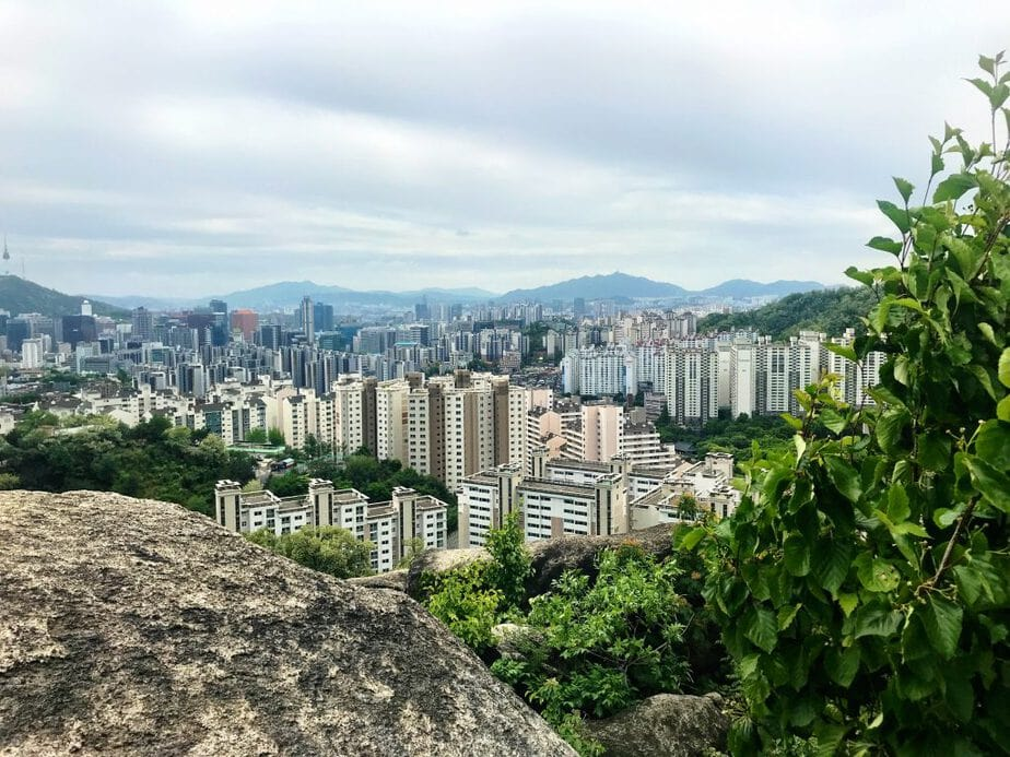 The city of Seoul with tall buildings and mountains in the background taken by a Digital Nomad working in the city