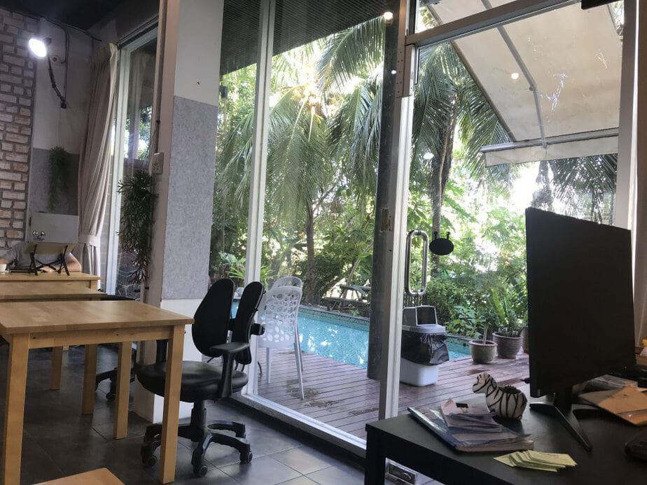 Windows in Hatch Coworking that look out onto a pool and tropical vegetation