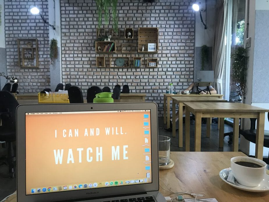 A laptop and cup of coffee on a table in a coworking space in Phuket