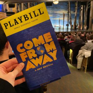 Come From Away Playbill held up in the theatre with the stage in the backround