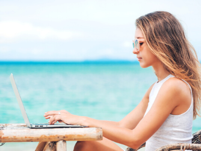 girl sitting in tank top and laptop at the beach