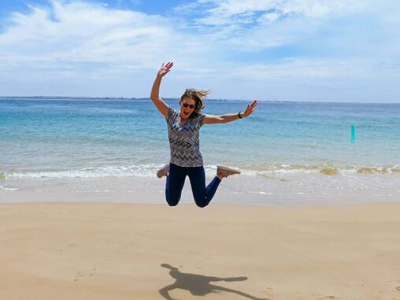 Traveling Tayler jumping on the beach in Australia