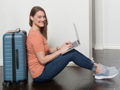 Traveling Tayler sitting with her laptop and suitcase