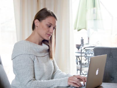Girl sitting at a desk with her laptop in a white cozy sweater