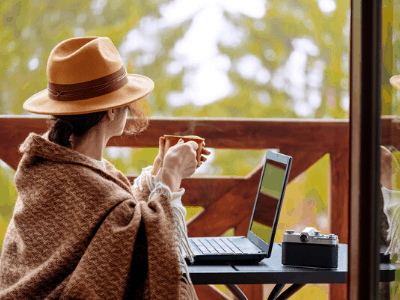 Woman sitting on a patio in the trees with a coffee, laptop and camera