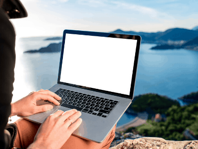 Man working from a laptop with a view of the ocean