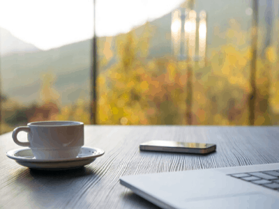 Laptop, Phone and coffee on a desk with trees in the background for a lucky remote worker