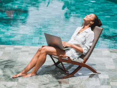 happy Woman with laptop sitting in a chair in a blue pool