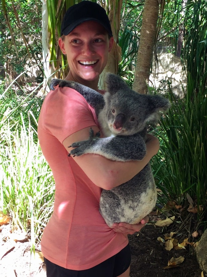 young girl in a pink shirt & hat is smiling while holding a Koala