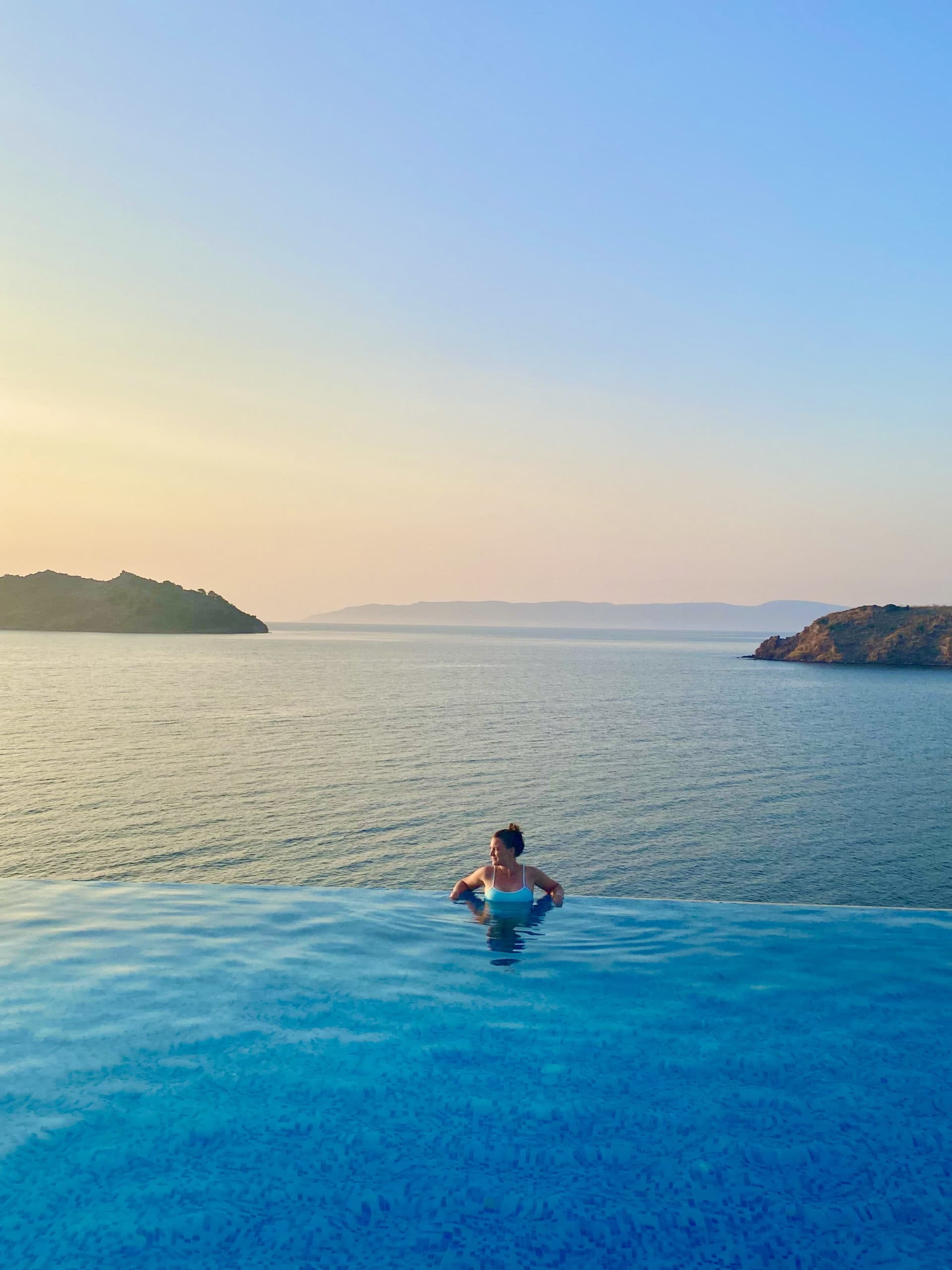 A woman casually stands in an infinity pool looking over her shoulder with the sea in the background
